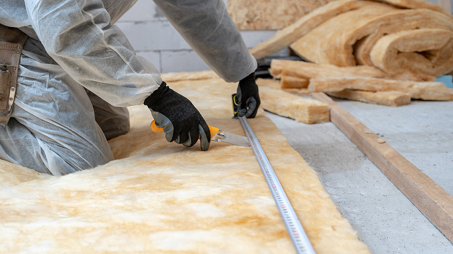 man cutting and measuring a insulation foam
