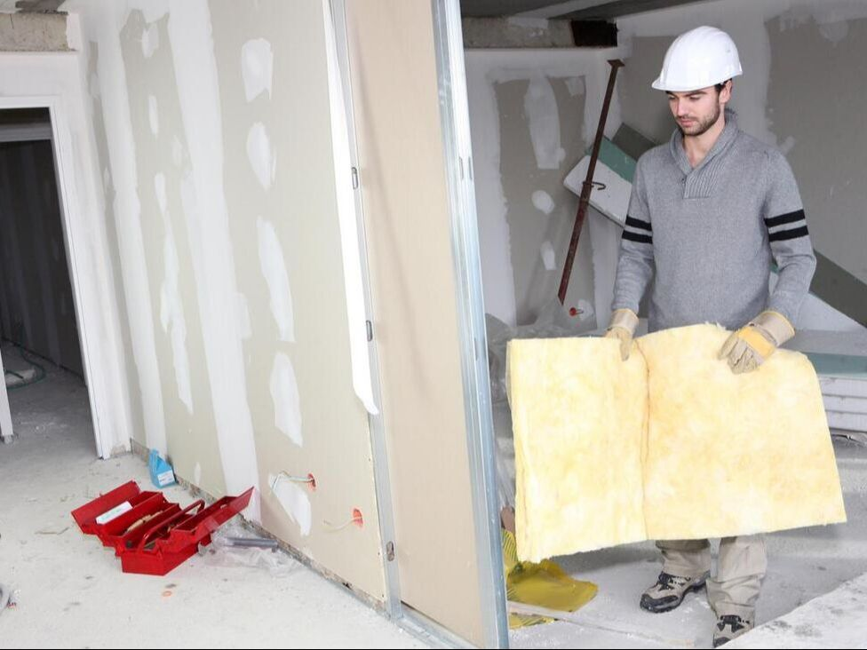 a man holding an insulation foam on a building